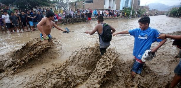 Moradores tentam atravessar rua inundada em Trujillo, no norte do Peru