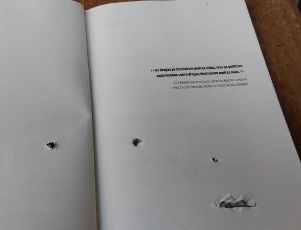 """""""As drogas já destruíram muitas vidas, mas as políticas equivocadas sobre drogas destruíram muitas mais"""". A frase, de Kofi Annan, ex-secretário-geral da ONU, estampa página de livro atingido por disparo em escola de música no Jacarezinho - Reprodução"""