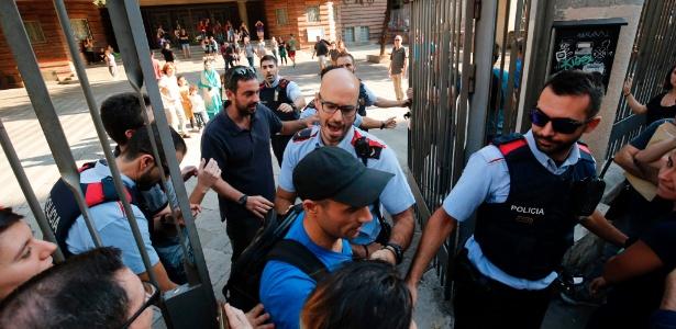 """29.set.2017 - Polícia catalã, conhecida como Mossos d""""Esquadra, tenta impedir a entrada de pessoas que tentavam ocupar uma das escolas que seriam usadas na votação de domingo - PAU BARRENA/AFP"""