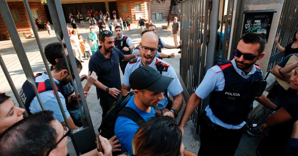 29.set.2017 - Polícia catalã, conhecida como Mossos d'Esquadra, tenta impedir a entrada de pessoas que tentavam ocupar uma das escolas que seriam usadas na votação de domingo