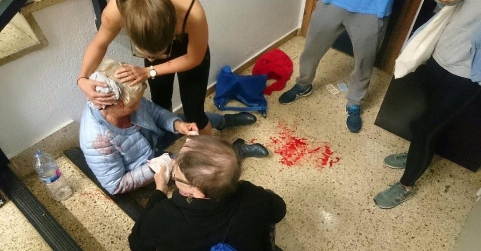 1º.out.2017 - Mulher ferida na cabeça é assistida por jovem em Barcelona durante o referendo que decide a independência da Catalunha. Não se sabe como ela se feriu