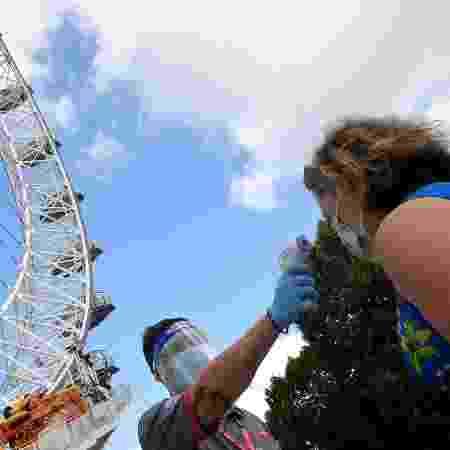 1.ago.2020 - Passageira mede a temperatura entes de embarcar na London Eye, a roda gigante mais famosa de Londres - Toby Melville/Reuters