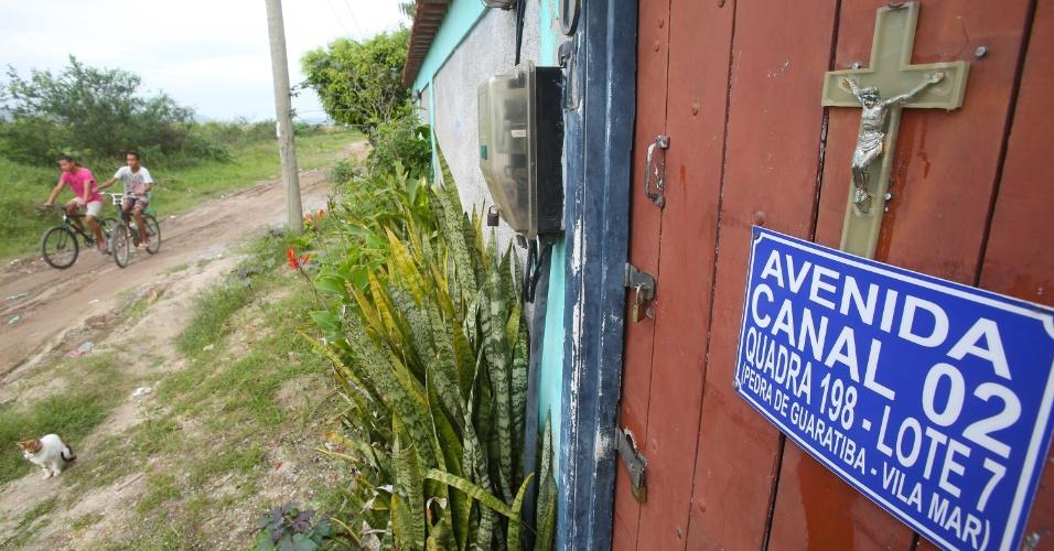 6.jul.2015 - Jovens passam de bicicleta na frente de casa com crucifixo na porta, em Guaratiba, na zona oeste, nas proximidades do terreno onde foi construído o Campus Fidei (Campo da Fé) da JMJ (Jornada Mundial da Juventude) de 2013