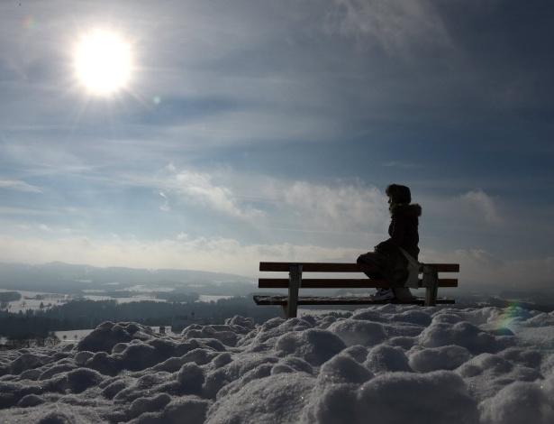 """20.jan.2016 - Jovem sentada em banco em local coberto de neve com Sol ao fundo parece """"flutuar nas nuvens"""". A foto foi feita em região montanhosa de Irschenberg, na Alemanha"""