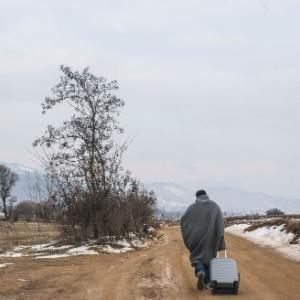 Refugiado carrega bagagem após cruzar a fronteira da Macedónia na Sérvia