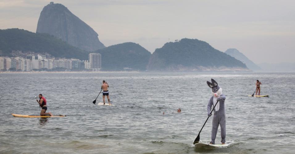 26.mar.2016 - Com fantasia de coelho da Páscoa, praticante de stand up paddle vira atração no mar da praia de Copacabana, na zona sul do Rio de Janeiro