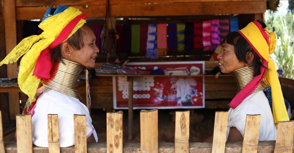 11.abr.2016 - Mulheres da tribo Padaung conversam em loja de presentes na vila Panipat, em Myanmar. Na cultura local, os primeiros anéis são colocados em volta do pescoço quando as meninas têm oito anos. Conforme as garotas vão crescendo, mais anéis vão sendo adicionados