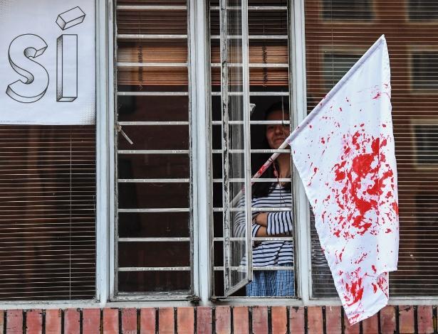 Bandeira manchada de vermelho é colocada em janela em Bogotá, na Colômbia, após resultado de referendo sobre acordo de paz com as Farc