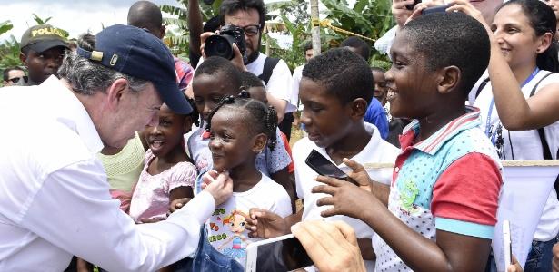 O presidente da Colômbia, Juan Manuel Santos, conversa com crianças no município de Bojayá