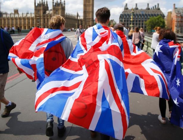 Pessoas enroladas em bandeiras do Reino Unido atravessam a Ponte Westminster, em Londres, três dias depois que os eleitores britânicos decidiram cortar os laços com a União Europeia.