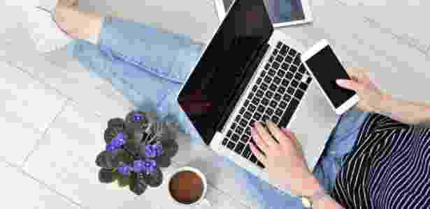 mulher trabalhando, trabalho, finanças pessoais, celular, computador - Getty Images - Getty Images