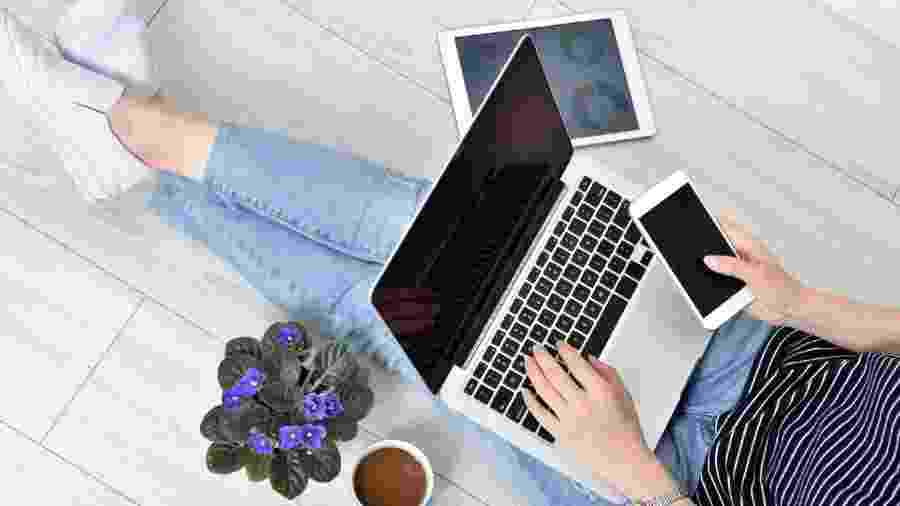 mulher trabalhando, trabalho, finanças pessoais, celular, computador - Getty Images