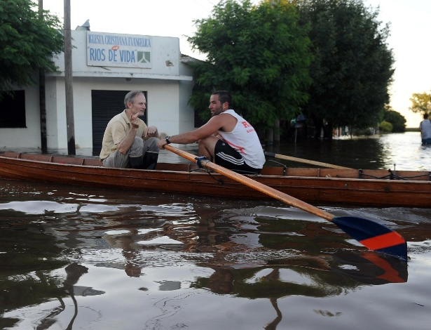 Residentes da cidade de La Emilia se locomovem em canoa por rua inundada