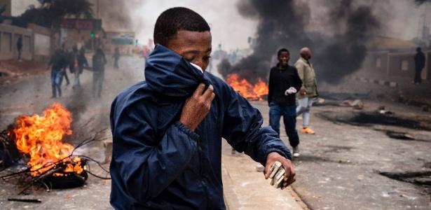 Manifestante protege o rosto da fumaça de gás lacrimogêneo durante protesto em Johannesburgo