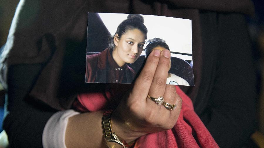 Renu Begum, irmã mais velha de Shamima Begum segura uma foto da irmã durante entrevista à imprensa britânica em 2015 - LAURA LEAN / POOL / AFP