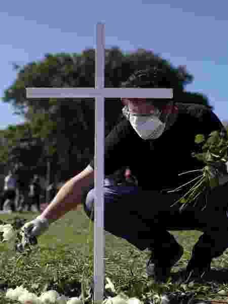 Homem coloca flores perto de uma cruz durante um protesto e tributo aos profissionais de saúde mortos por coronavírus em São Paulo - Amanda Perobelli/Reuters