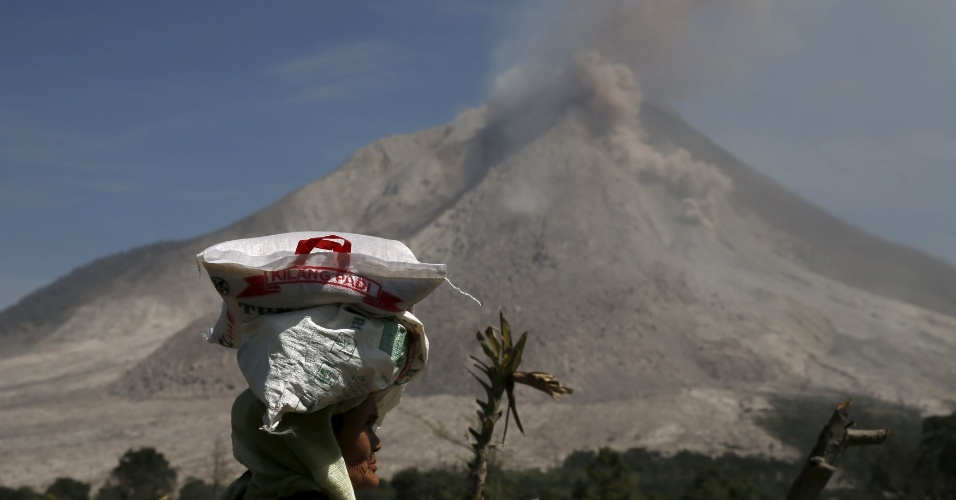 29.jun.2015 - Moradora carrega saco de arroz na cabeça enquanto após receber doação de comida próximo ao vulcão Sinabung, em Karo, no norte de Sumatra, Indonésia, nesta segunda-feira (29). Mais de 10 mil pessoas de 12 vilarejos deixaram suas casas e foram removidas para campos de refugiados, devido a erupção do vulcão