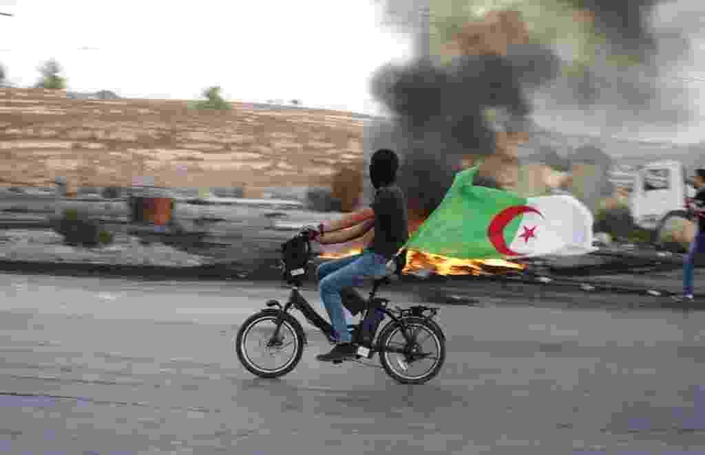 """14.out.2015 - Jovem palestino carrega bandeira argelina enquanto pedala em meio a confrontos entre manifestantes palestinos e o Exército isralense. A escalada da violência entre israelenses e palestinos nas últimas semanas tem despertado temores de que se inicie uma terceira """"intifada"""" palestina - Abbas Momani/AFP"""