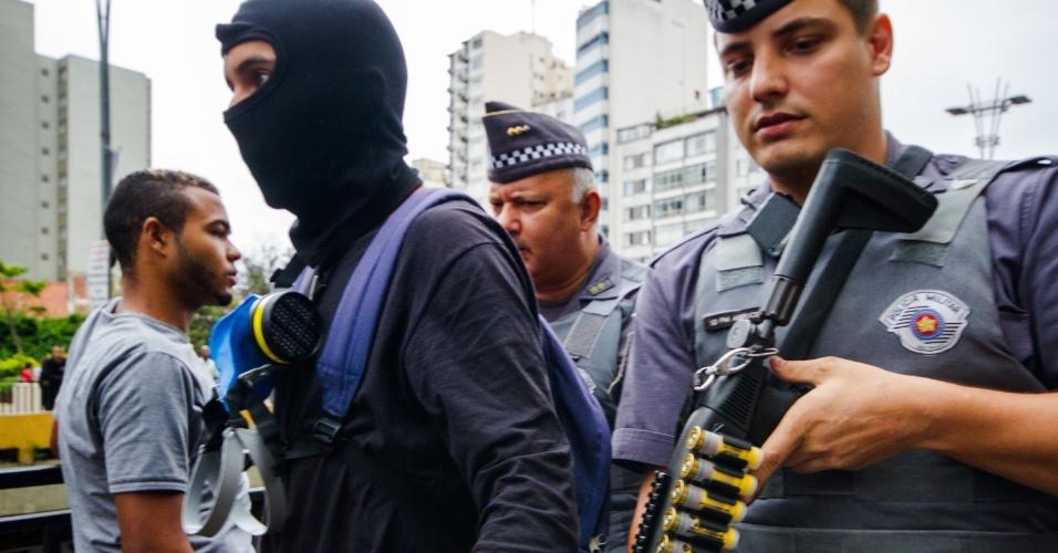 12.jan.2016 - Policial revista manifestantes antes de protesto contra o aumento das tarifas do transporte público em São Paulo (SP). Presença de agentes de segurança é intensa na Avenida Paulista, onde grupo se reúne para contestar o aumento de R$ 3,50 para R$ 3,80