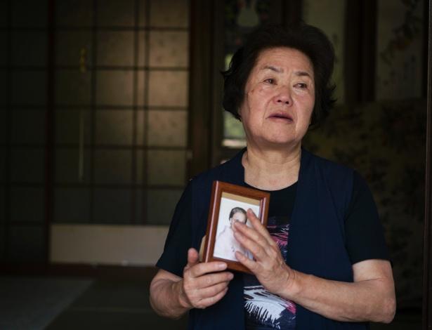 Miyako Jodai, 76, sobrevivente do bombardeio atômico de Nagasaki, no Japão, segura foto de sua tia, que a criou