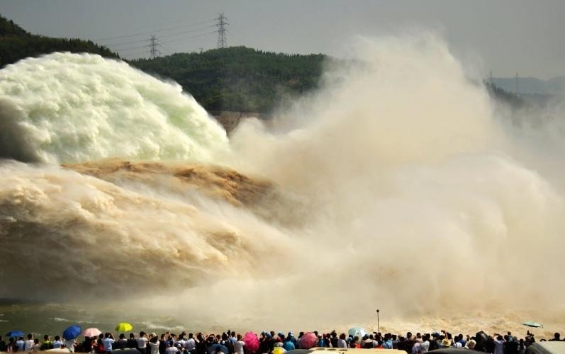 3+jul.2016 - Curiosos observam a queda d'água na represa Xiaolangdi, no rio Rio Amarelo, em Jiyuan (China). Com as comportas abertas para liberar o excesso, o escoamento da água acaba virando um espetáculo para os observadores