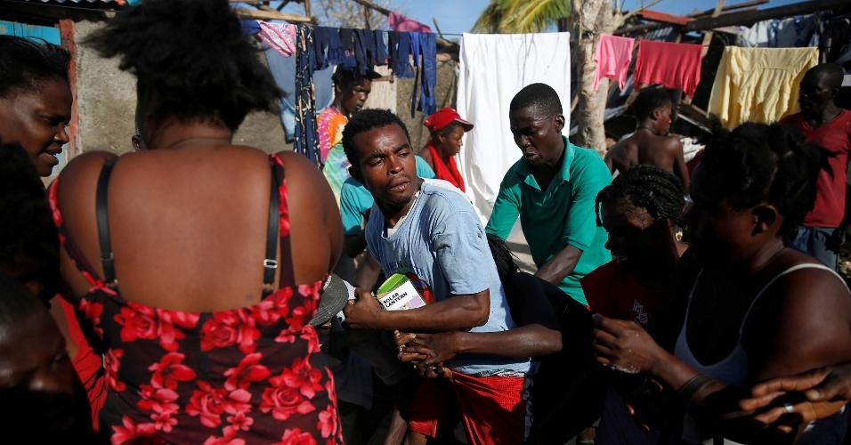 8.out.2016 - Moradores de Jeremie, no Haiti, disputam lanternas levadas pelo presidente interino do país, Jocelerme Privert, que visitou o local após a passagem do furacão Matthew
