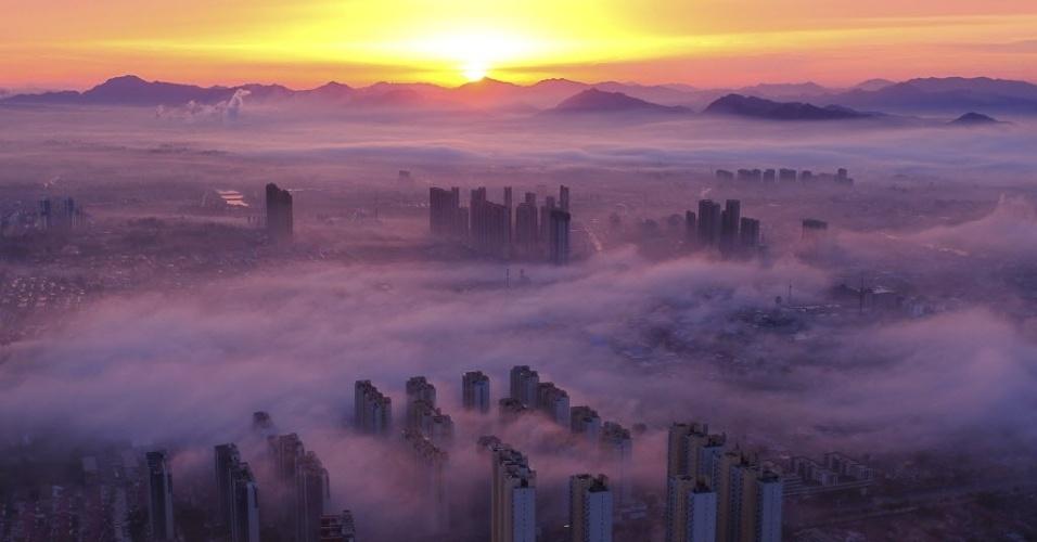 28.out.2016 - Edifícios são camuflados pela névoa do amanhecer na província de Hebei, norte da China