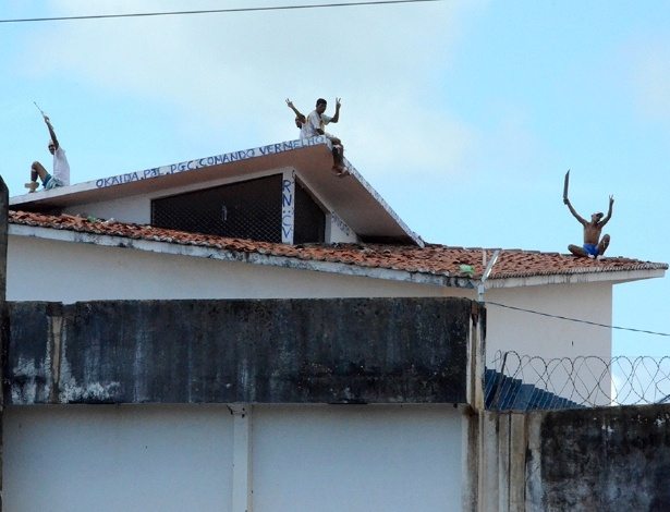 Presos exibem facões do alto do telhado de um dos pavilhões do presídio Alcaçuz, em Nísia da Floresta (RN)