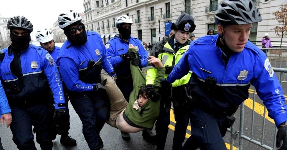 20.jan.2017 - Policiais carregam manifestante que foi detido durante protesto contra posse do presidente dos EUA, Donald Trump, nesta sexta-feira (20), em Washington DC