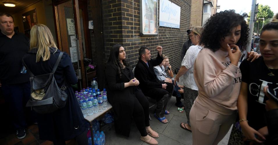 14.jun.2017 - Nas proximidades do prédio incendiado, pessoas se mobilizam para ajudar vítimas com água e outros suprimentos