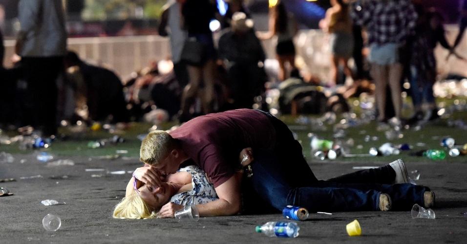 1º.out.2017 - Um homem deita-se sobre mulher durante ataque de atirador