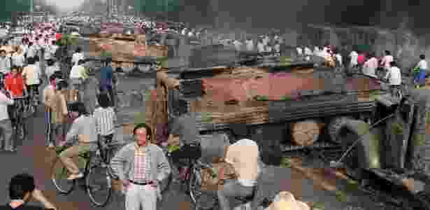 Imagem de 4 de junho de 1989 mostra moradores de Pequim passando por veículos militares queimados por manifestantes durante os confrontos na Praça da Paz Celestial - Manny Ceneta/ AFP