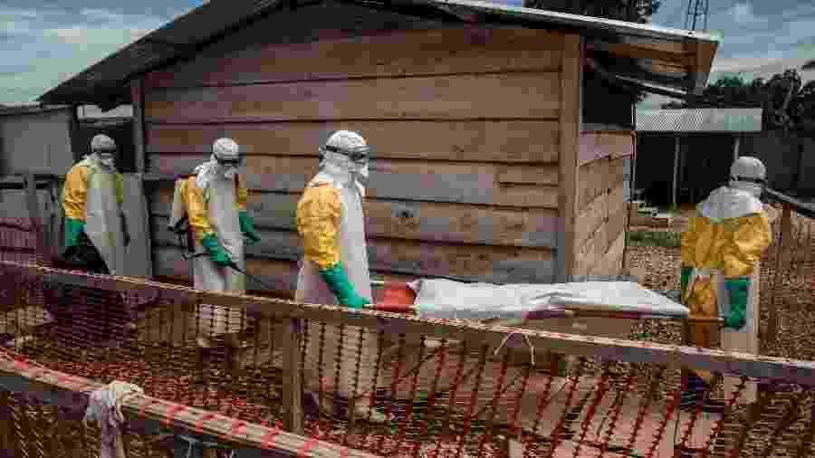 """Profissionais carregam o corpo de uma menina de 11 anos que morreu de ebola depois de ter sido internada em um centro de tratamento em Beni, no Congo - Finbarr O""""Reilly/The New York Times"""