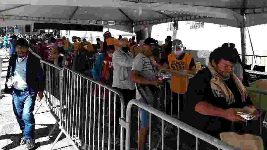 Pessoas retiram marmita com almoço e suco distribuídos por franciscanos e voluntários em tenda no Largo São Francisco, no centro de São Paulo - Marcelo Oliveira/UOL