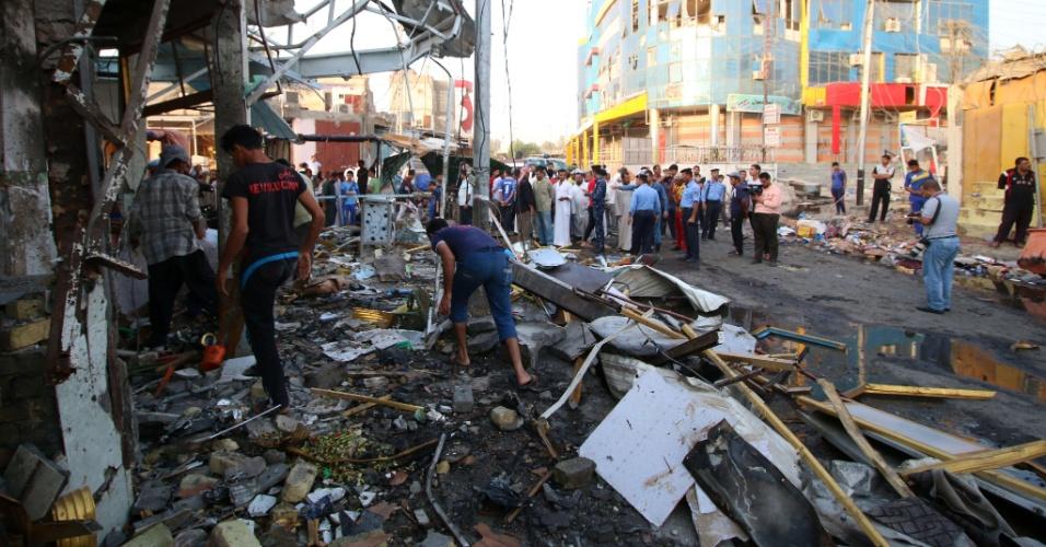 6.out.2015 - Iraquianos vasculham os destroços do local em Bagdá onde explodiu um dos três carros-bombas que foram detonados no país nesta segunda-feira (5). Os atentados deixaram menos 50 pessoas mortas em Bagdá e na cidade de Basra
