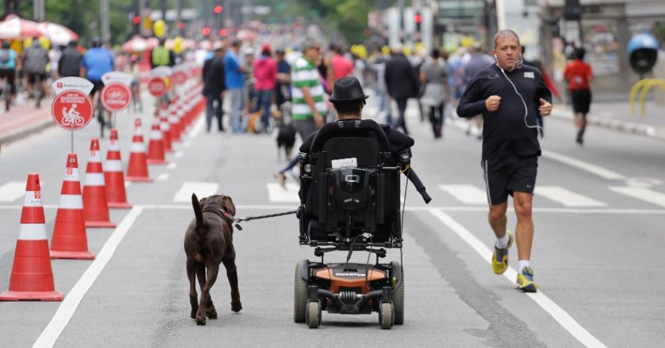 18.out.2015 - Em sua cadeira elétrica, homem leva cão para um passeio pela avenida Paulista sem a circulação de carros. Depois de dois testes realizados em junho e agosto, a prefeitura decidiu fechar a via para carros aos domingos, das 9h às 17h