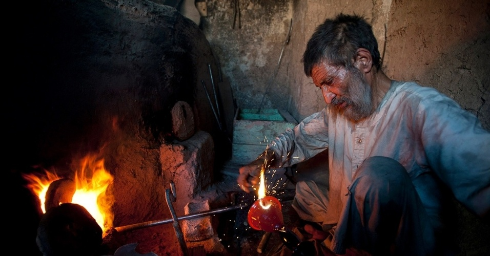 11.dez.2015 - Um artesão afegão trabalha numa peça de vidro azul. Em Herat, onde a arte em vidro já foi tradicional, restam poucos artesãos