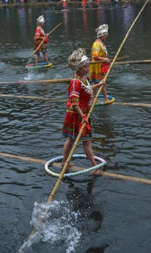 2.jan.2016 - Mulheres participam de prova de equilíbrio sobre bambus em festival tradicional na cidade de Guiyang, na China. Essa é uma das modalidade dos jogos realizados anualmente no rio Huaxi para celebras o Ano-Novo