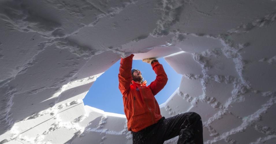 21.jan.2016 - O diretor da vila de iglus, Reto Gilli, ajeita os últimos blocos de neve durante a construção do maior iglu do mundo