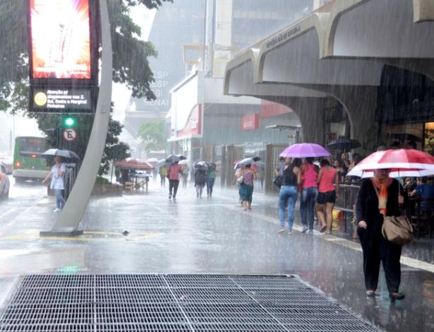 Pedestre enfrenta chuvas na Avenida Paulista, em São Paulo, SP, nesta tarde de quinta-feira