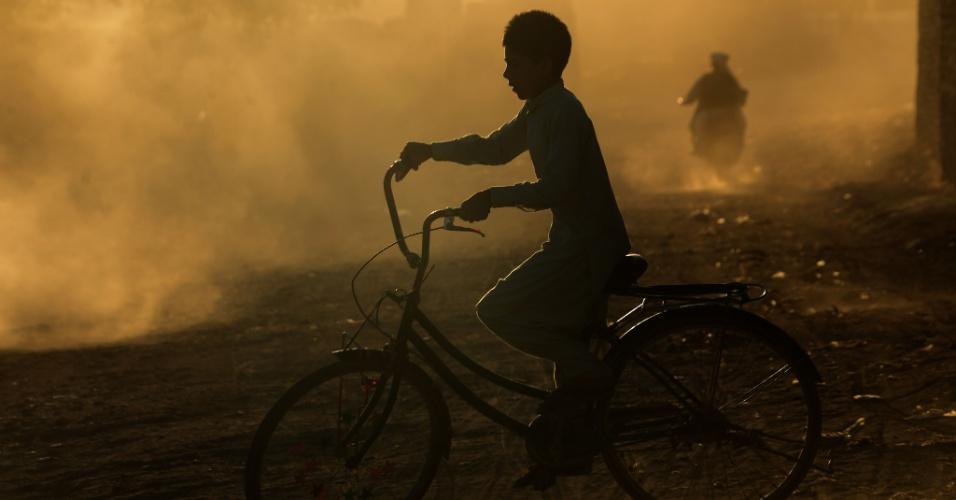 2.set.2016 - Menino afegão anda de bicicleta entre a poeira de uma estrada nos arredores de Herat