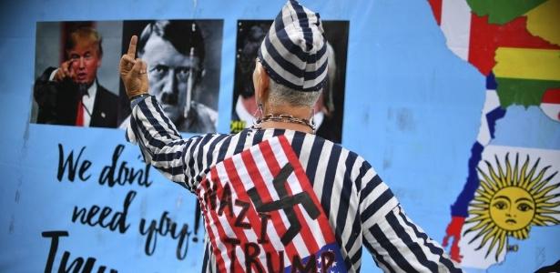 Manifestante usa imagem de Donald Trump e Adolf Hitler durante protesto