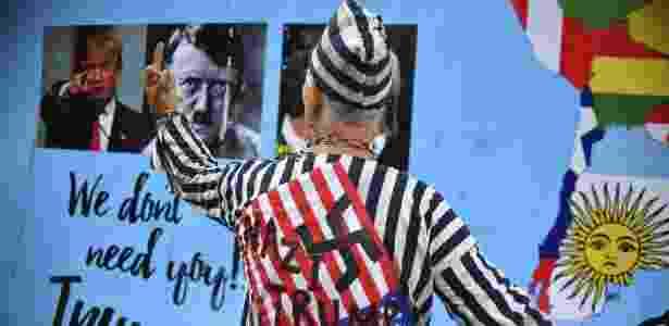 Manifestante usa imagem de Donald Trump e Adolf Hitler durante protesto  - Yuri Cortez/AFP