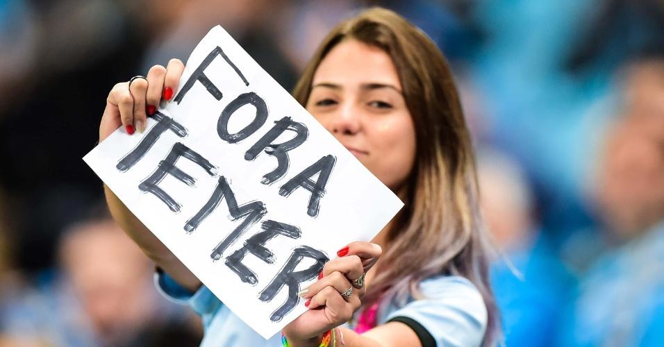 """17.mai.2017 - Torcedora do Grêmio empunha um """"Fora, Temer"""" durante a partida contra o Fluminense, válida pela Copa do Brasil 2017, na Arena do Grêmio em Porto Alegre. Presidente foi acusado de ter dado aval para a compra do silêncio do ex-deputado Eduardo Cunha"""