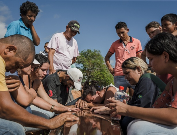 Familiares e amigos choram durante enterro de uma das vítimas do massacre