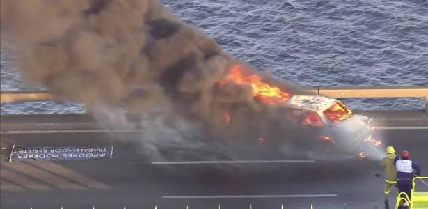 """Carro incendiado ao lado de faixa: """"Podres poderes. Trabalhador resiste"""" - Reprodução/TV Globo"""