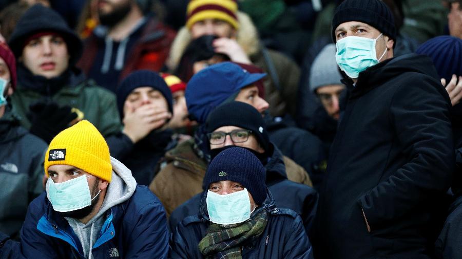 27.fev.2020 -  Torcedores usam máscaras em meio à preocupação com o coronavírus antes da partida Gent v AS Roma pela Europa League - Francois Lenoir / Reuters