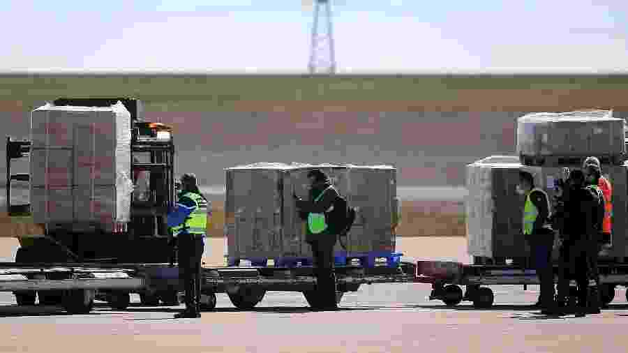 Funcionários do aeroporto descarregam avião que transportava 10 milhões de máscaras encomendadas pela França da China - François Nascimbeni/AFP