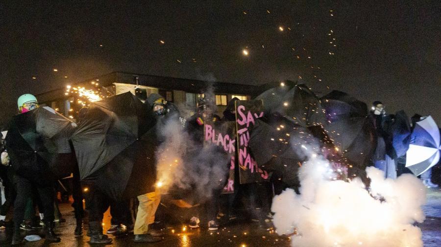 13.abr.2021 - Manifestantes se protegem com guarda-chuvas contra gás lacrimogêneo disparado pela polícia em protesto contra a morte de Daunte Wright - Kerem Yucel/AFP