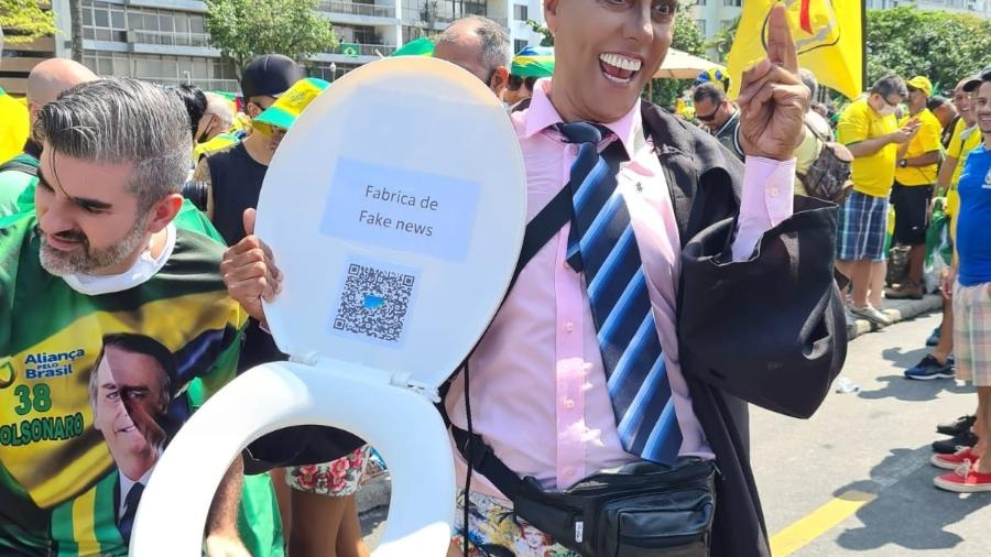 """7.set.2021 - Homem aparece fantasiado de ministro Alexandre de Moraes, do STF, no Rio de Janeiro, em protesto a favor de Bolsonaro. Ele carrega um assento de privada onde há um papel com a frase """"fábrica de fake news"""" - Elisa Soupin/UOL"""